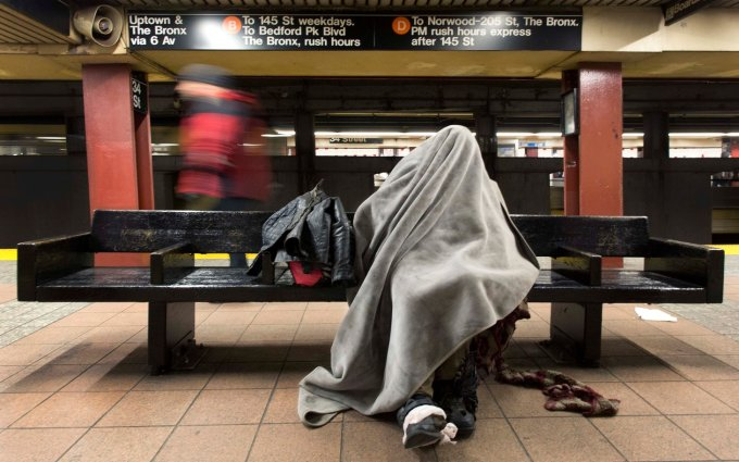 A homeless man rests under a blanket while sitting on a bench in a New York subway station, Tuesday, Jan. 28, 2014. Monday night volunteers spread throughout the city to do an annual count of homeless people living on the streets. According to advocacy group Coalition for the Homeless, more than 50,000 people live in municipal homeless shelters, with thousands more living on the streets. (AP Photo/Mark Lennihan)